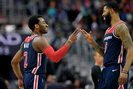 Washington Wizards guard John Wall (2) reacts with forward Markieff Morris (5) during the second half of the tea's NBA basketball game against the Boston Celtics, Tuesday, April 10, 2018, in Washington. The Wizards won 113-101. (AP Photo/Nick Wass)