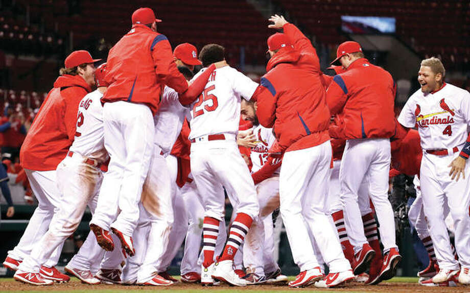 Cardinals' Matt Carpenter (13) is surrounded by teammates as he steps on home after hitting a walk-off home run in the 11th inning Tuesday against the Milwaukee Brewers in St. Louis. The Cardinals won 5-3. Photo:       AP
