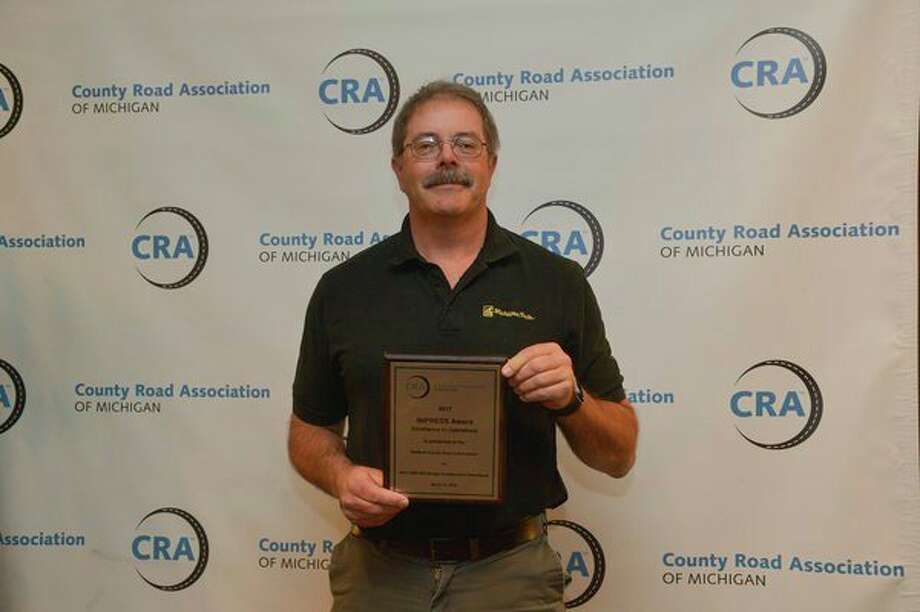 Terry Palmer, managing director for Midland County Road Commission, holds an IMPRESS Award from the County Road Association of Michigan. (Photo provided)