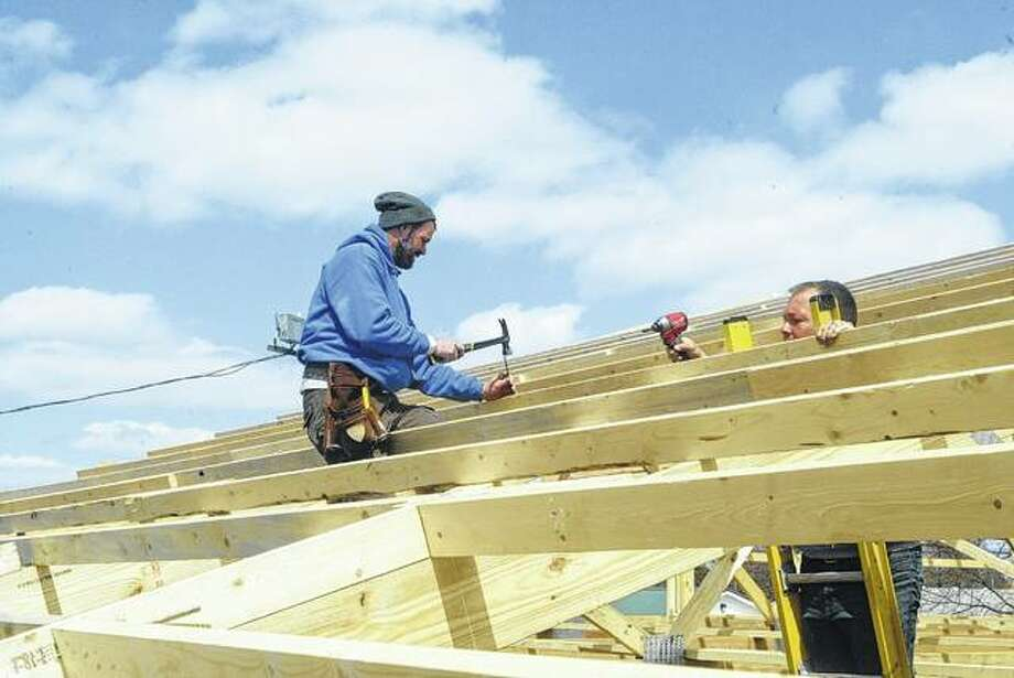 Morgan County Fair Board members Luke Armstrong (left) and Mark Stiltz work Tuesday on the rafters of the new poultry barn at the fairgrounds. The 40-foot by 60-foot building replaces a smaller barn that recently was demolished. Armstrong said the new building is part of the fair board's ongoing efforts to improve the fairgrounds.