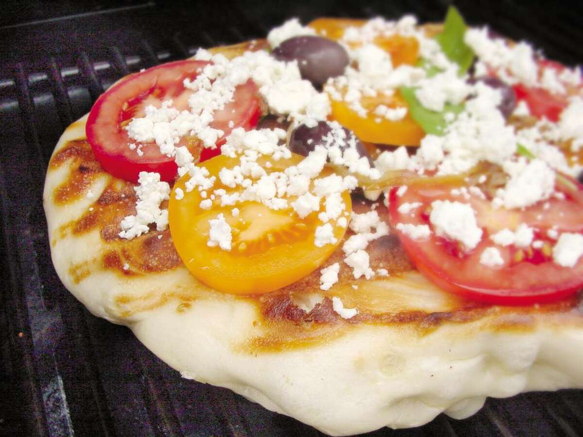 Impress your guests by griling a pizza with tomatoes, feta cheese and kalamata olives, below. (Times Union archive)