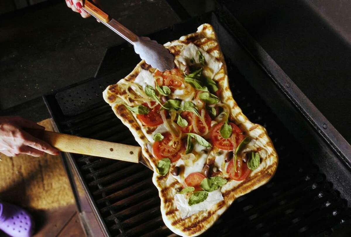 Spraying your grill with cooking spray before it heats up will make flipping the pizza dough easier. If you don't own a pizza peel, use a rimless baking sheet to slide the dough onto the grill. Use a spatula and tongs to lift it off the grill when it?s done. (Carol Lawrence / Colorado Springs Gazette)