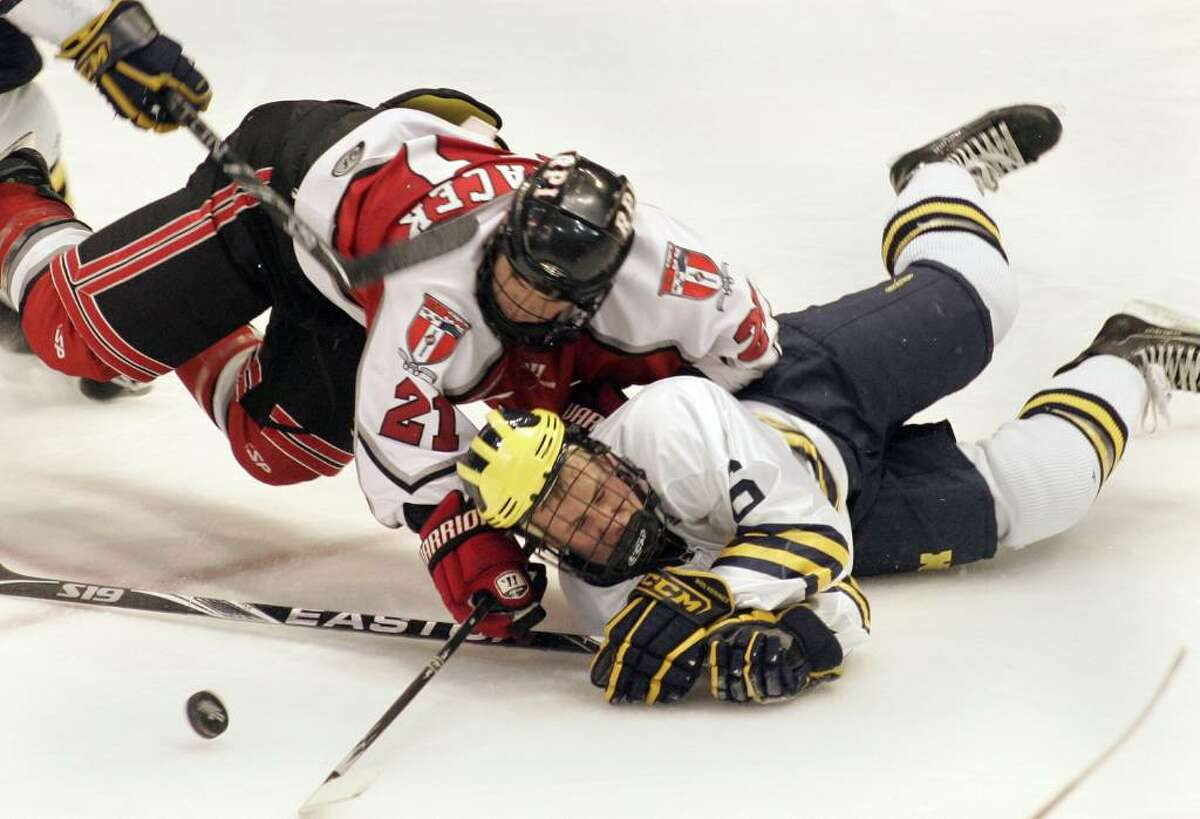 RPI's Chase Polacek, left, challenges Michigan's Brandon Burlon for the puck. (AP Photo/Jerry S. Mendoza)