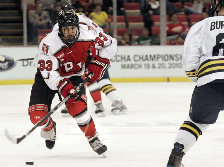 RPI's Jordan Watts pushes the puck down ice against Michigan. (AP Photo/Jerry S. Mendoza)