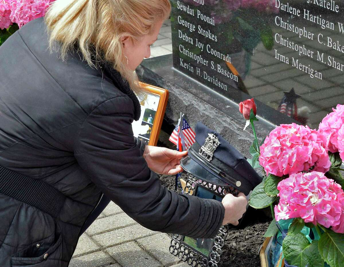 Paula Carponello-Goca places her late husband Rensselaer Police Officer Mark Goca's uniform hat at the base of the Rensselaer County DWI Victims Memorial during a ceremony April 10, 2018 in Troy, NY. (John Carl D'Annibale/Times Union)