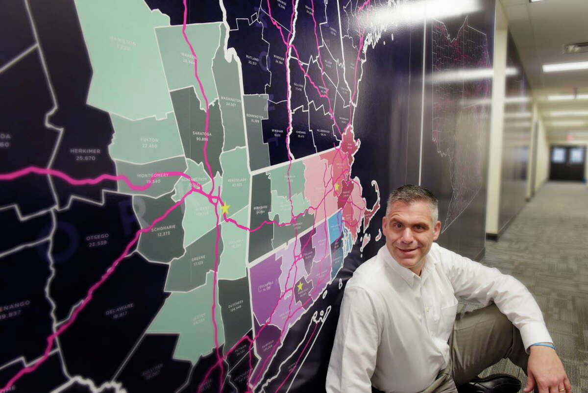 Rick Drake, the new CFO of Elevation Ten Thousand and Catseye USA, poses next to a wall wrap that shows the Catseye Pest Control market territories on Wednesday, April 4, 2018, in Latham, N.Y. (Paul Buckowski/Times Union)
