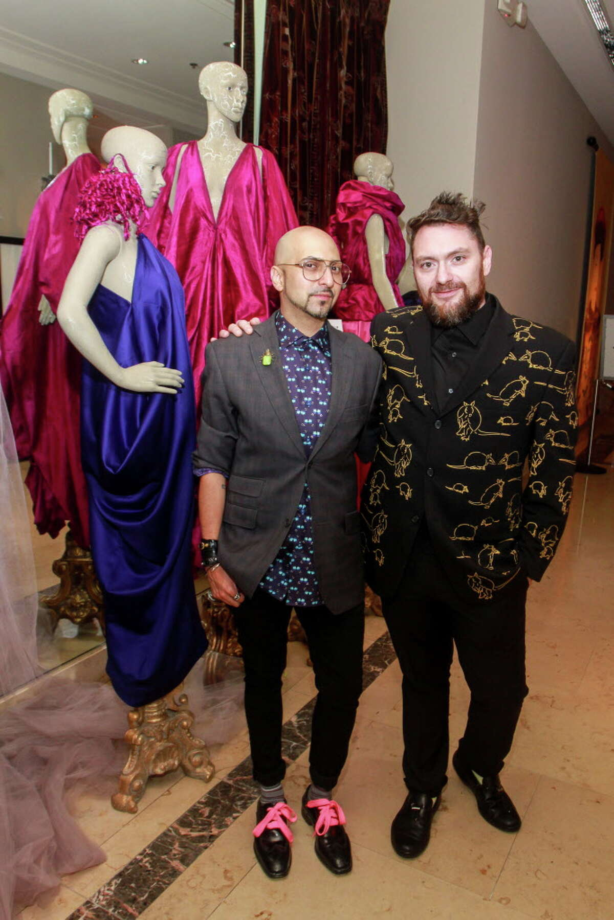 René Garza, left, and John Abodeely at the Houston Arts Alliance dinner. They are standing in front of René's designs.