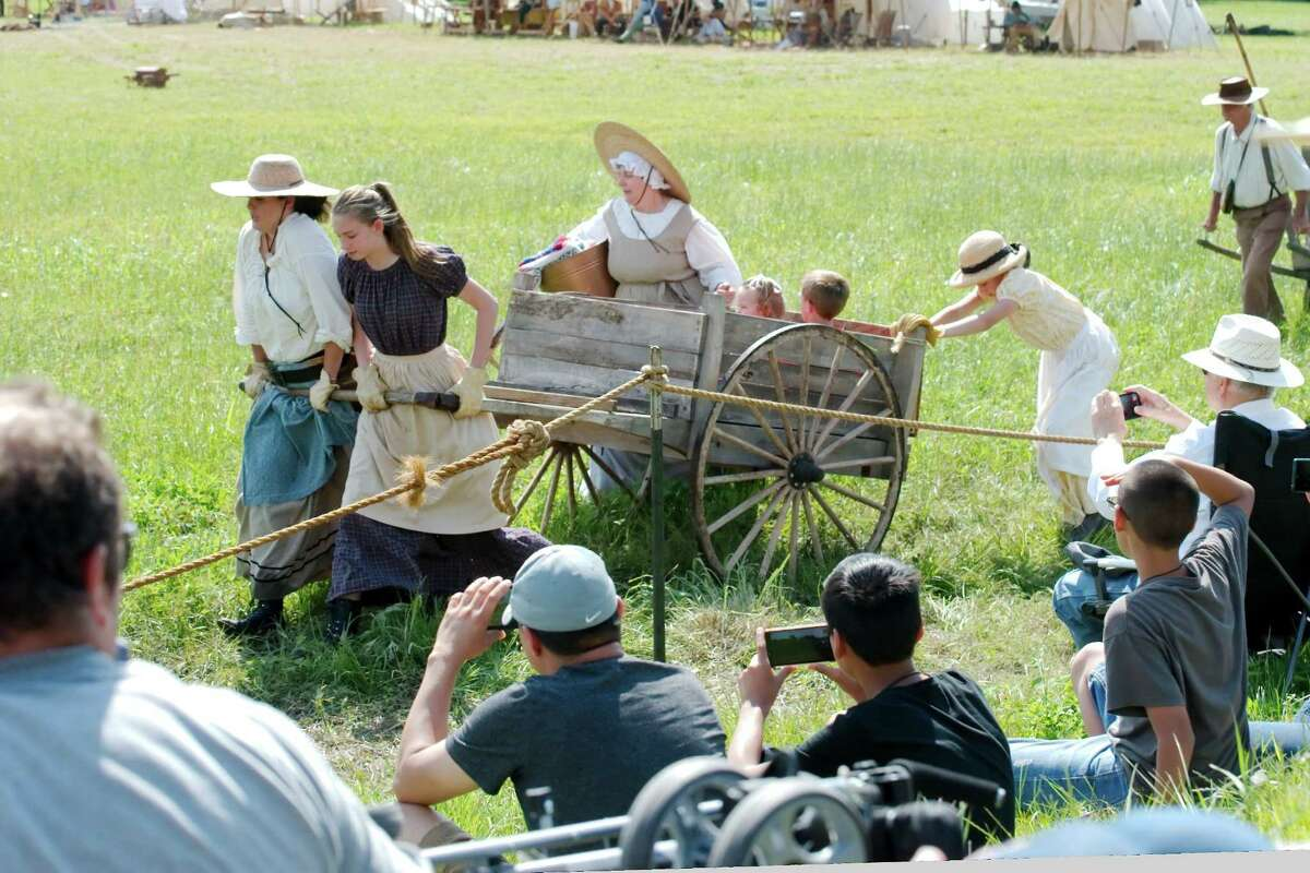 History enthusiasts push a wooden wagon to portray life during a runaway scrape that might have taken place in the months prior to the Battle of San Jacinto during a re-enactment of the battle.