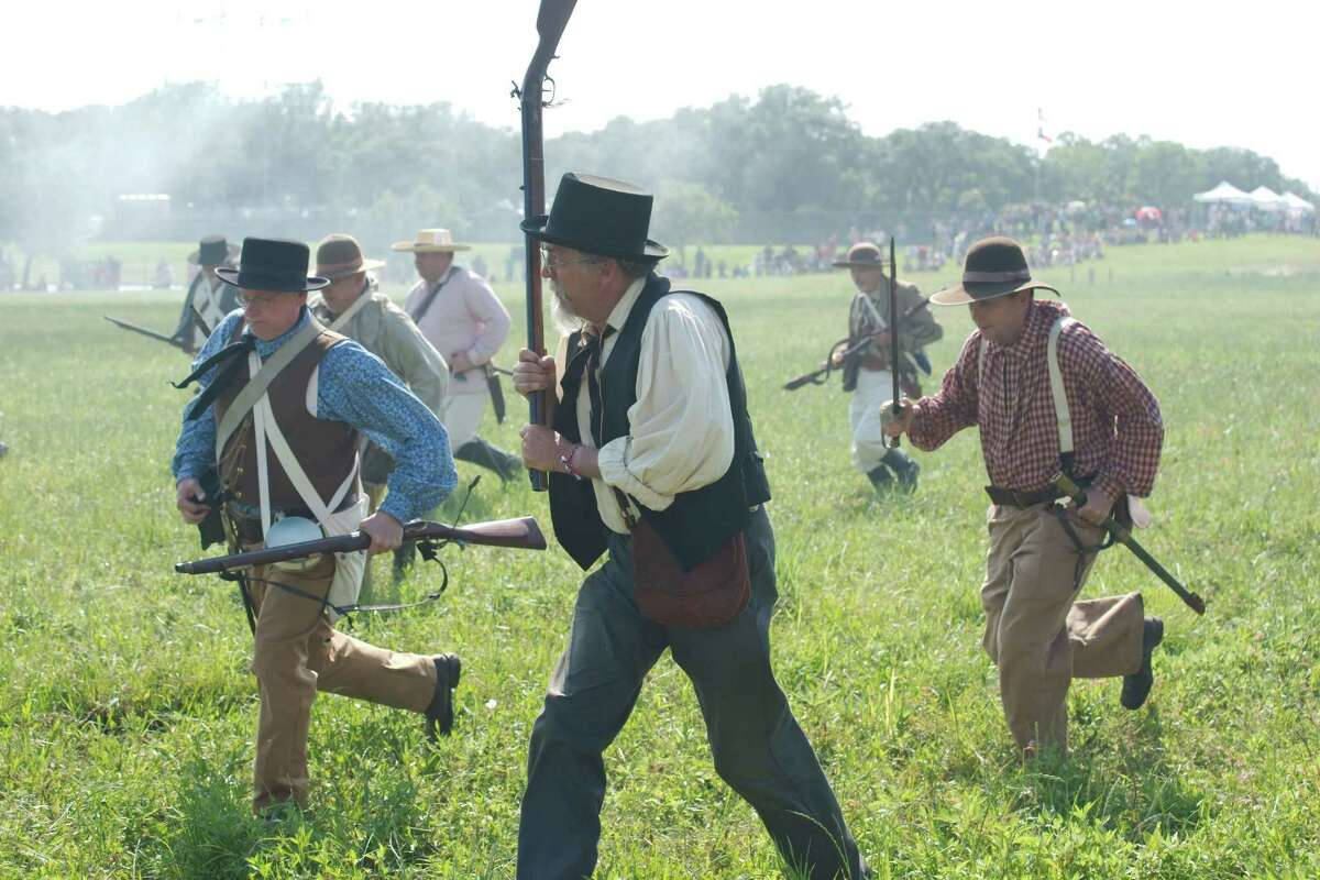 History enthusiasts wear replica clothing and fire historically accurate muskets used by Sam Houston's Texas volunteer army in the Battle of San Jacinto during a reenactment of the battle.