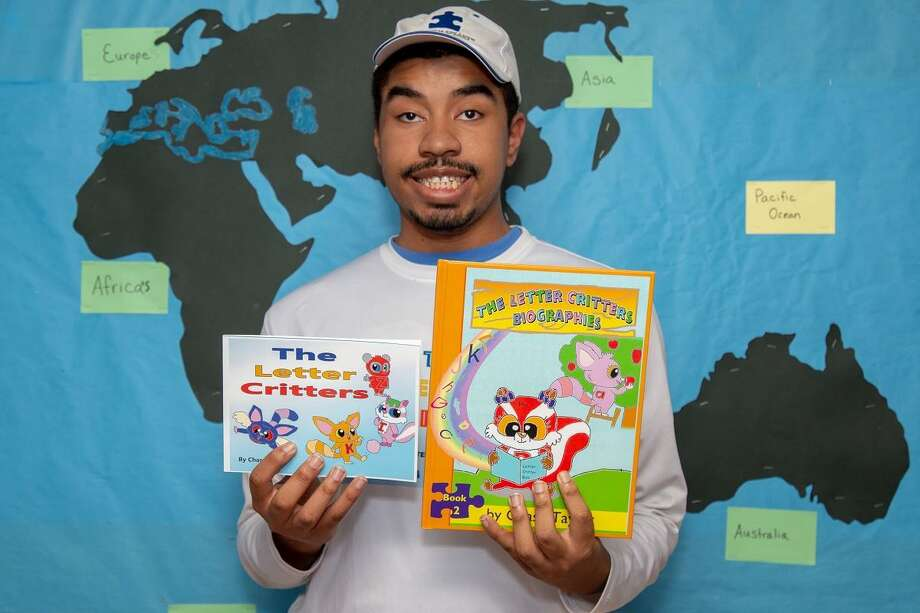 "Chase Taylor, 18, holding his first two books in ""The Letter Critter Series."" Chase, who has autism, authored and illustrated the engaging books, which he brought to an autism event at   Brennan Rogers School of Communications and Media in New Haven. Photo: Pam McLoughlin / Photo By Helen Taylor"