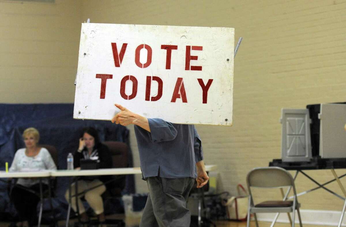 """File photo from May 2015 of Democratic Registrar of Voters Nancy Ryan carrying a """" Vote today"""" sign to the parking lot of the Municipal Center to help guide voters to the right place."""