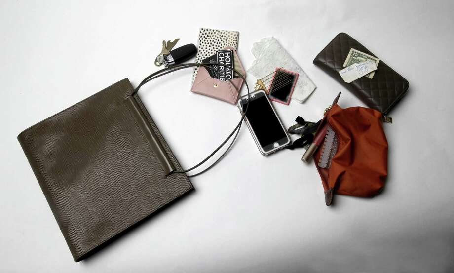My tote is filled with all sorts of work materials, tools and emergency needs. It's a fun bag because it holds everything that gets me through my work day, which is why my personal bag is not cluttered. Photo: Juanito M Garza /San Antonio Express-News / San Antonio Express-News
