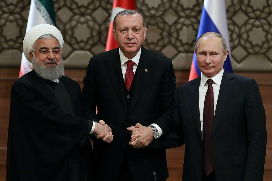 Iran's President Hassan Rouhani, Turkey's President Recep Tayyip Erdogan and Russia's President Vladimir Putin shake hands at a press conference after their second summit meeting in six months. Photo: Adem Altan / AFP / Getty Images