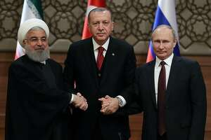 TOPSHOT - (LtoR) Iran's President Hassan Rouhani, Turkey's President Recep Tayyip Erdogan  and Russia's President Vladimir Putin shake hands after a joint press conference as part of a tripartite summit on Syria, in Ankara, on April 4, 2018.  The presidents of Iran, Turkey and Russia met on April 4, 2018 for their second tripartite summit in under six months, aiming to speed the peace process for Syria and bolster their influence in the country. / AFP PHOTO / ADEM ALTANADEM ALTAN/AFP/Getty Images