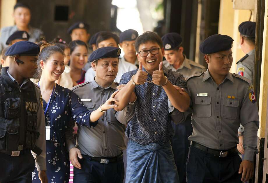 With wife Pan Ei Mon by his side, Reuters journalist Wa Lone gives a thumbs-up sign as he is escorted by police at his trial in Yangon, Myanmar. Wa Lone could face up to 14 years in prison. Photo: Thein Zaw / Associated Press
