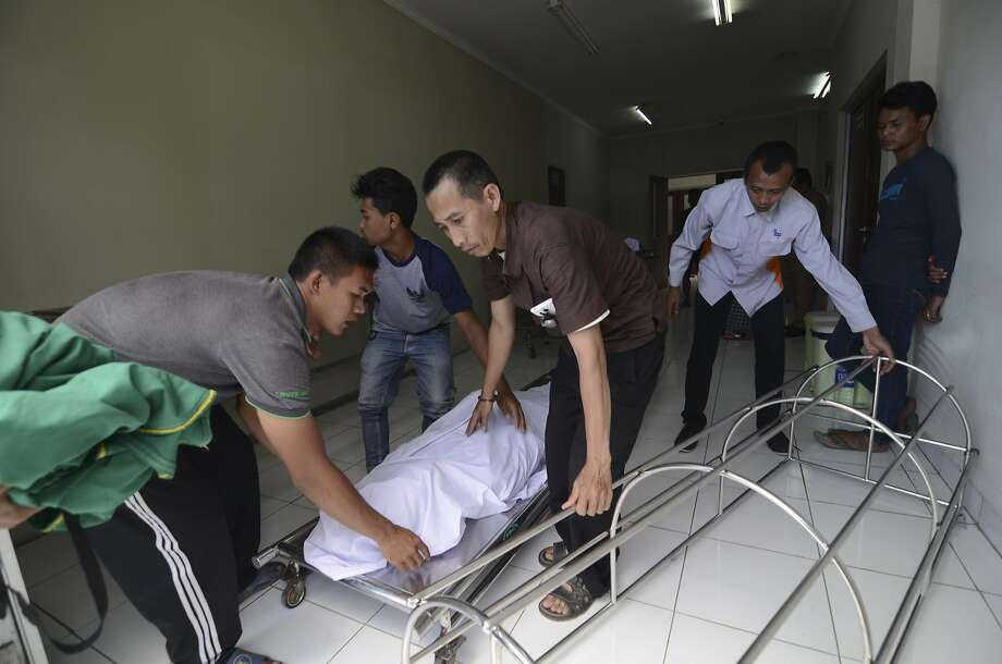 A family moves the body of a relative who died from drinking bootleg liquor at a hospital in Cicalengka, West Java, Indonesia. Some toxic liquor is sold in small clear plastic bags for $1.80. Photo: Associated Press