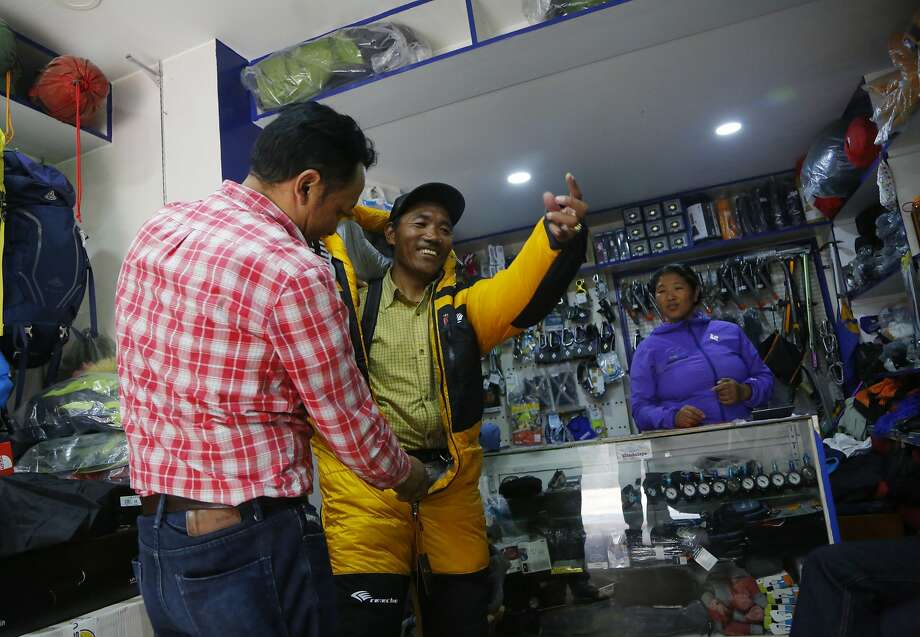 Kami Rita (center) checks out climbing gear in Kathmandu. He is one of three people to have scaled Mount Everest 21 times. Photo: Niranjan Shrestha / Associated Press