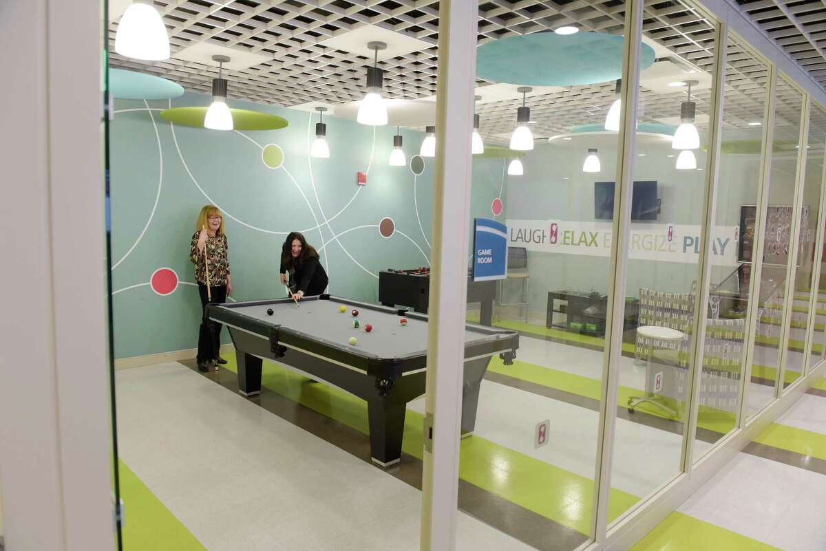 CAP COM employees play a game of pool in the game room at CapCom Headquarters on Tuesday, March 13, 2018, in Colonie, N.Y. (Paul Buckowski/Times Union)