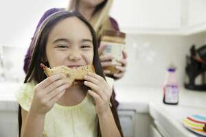 This stock image girl wisely eats her peanut butter and jelly sandwich at home instead of in a shopping cart at Target.