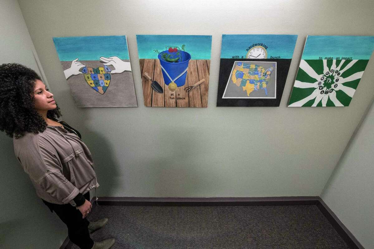 Crystal Brandow shows of some of the artwork on display at the Policy Research Associates Thursday March 15, 2018 Delmar, N.Y. (Skip Dickstein/Times Union)