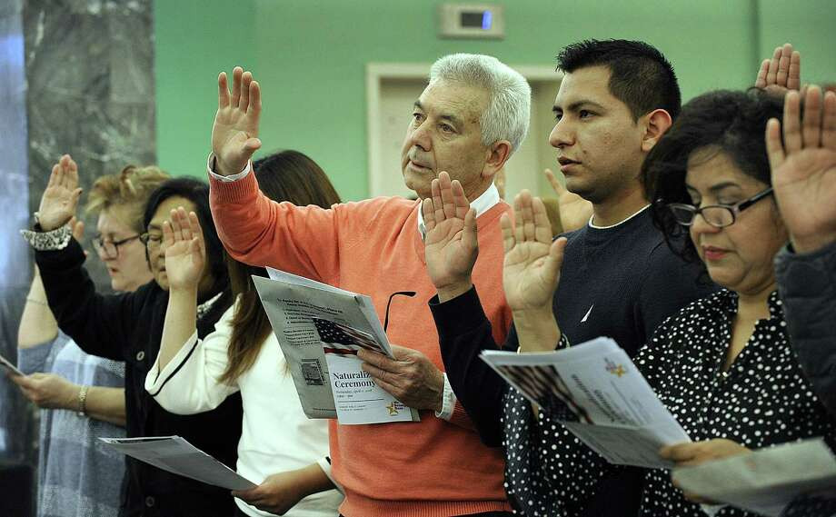 Albino Marinho, 64, center, an immigrant from Portugal, Francisco Gonzalez, 25, and Guadalupe, 50, immigrants from Mexico take the oath of citizenship Wednesday. A naturalization ceremony is held at the Danbury Library Wednesday, April 11, 2018. Photo: Carol Kaliff / Hearst Connecticut Media / The News-Times