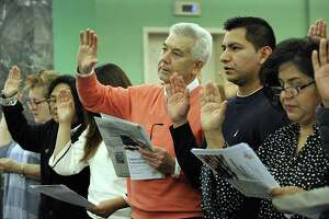 Albino Marinho, 64, center, an immigrant from Portugal, Francisco Gonzalez, 25, and Guadalupe, 50, immigrants from Mexico take the oath of citizenship Wednesday. A naturalization ceremony is held at the Danbury Library Wednesday, April 11, 2018.
