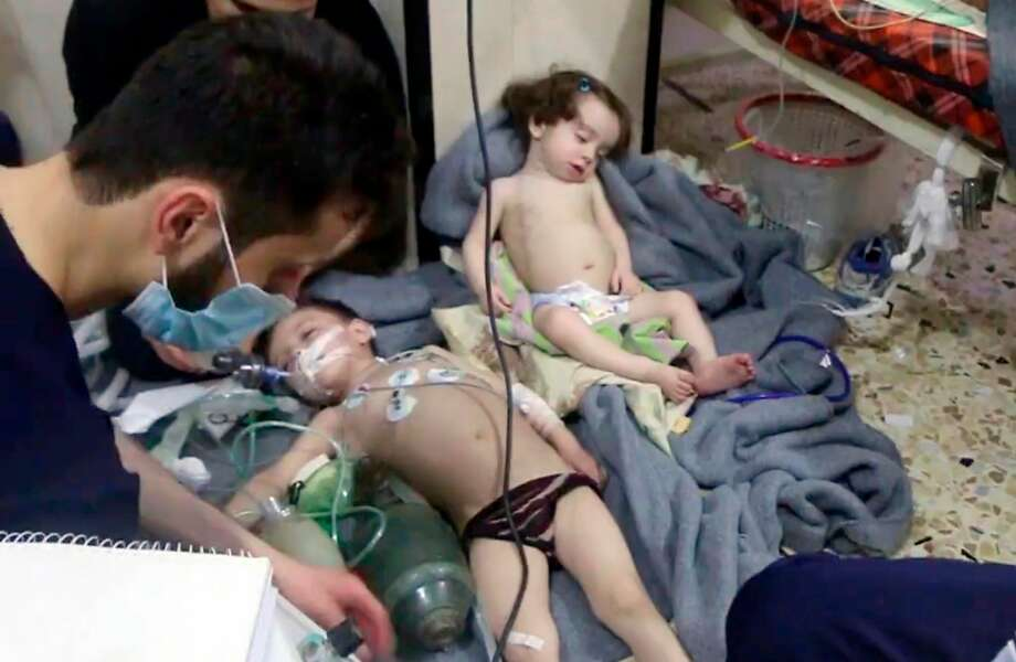 FILE - This Sunday, April 8, 2018 file image made from video released by the Syrian Civil Defense White Helmets, shows medical workers treating toddlers following an alleged poison gas attack in the opposition-held town of Douma, near Damascus, Syria. With the Middle East on edge and many fearing inadvertent triggering of regional war, it is easy to forget that two weeks ago Trump shocked advisers in declaring an intention to withdraw troops from Syria. Now, apparently angered by a suspected chemical attack, Trump is threatening imminent military strikes against the Syrian government forces he blames and rattling a saber at Syria's patron Russia. (Syrian Civil Defense White Helmets via AP, File) Photo: Associated Press