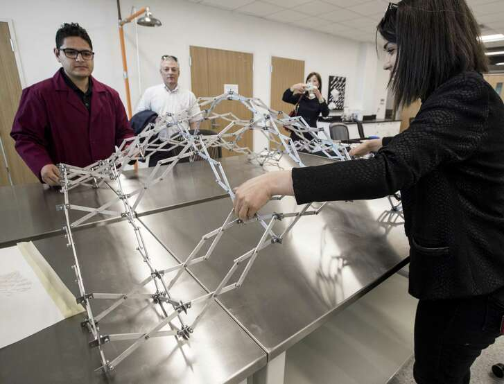 Abhinav Bhardwaj, Ph.D. student, left, and Dr. Nagar Kalantar, director of Advanced Infastructure Manufacturing and Material Lab, demonstrate a deployable structure during the opening of the Center for Infrastructure Renewal at Texas A&M on Wednesday, April 11, 2018, in Bryan, Texas. ( Brett Coomer / Houston Chronicle )