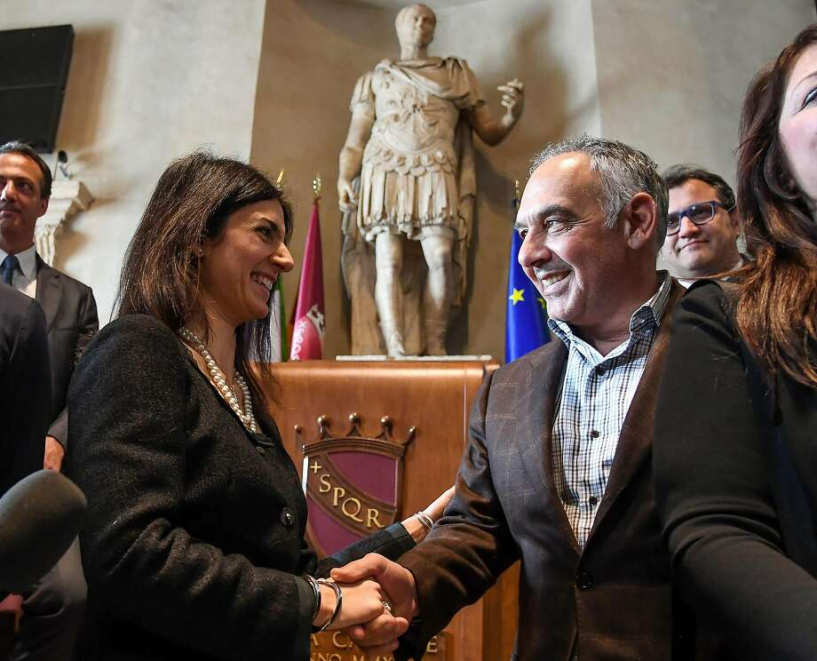 Roma president James Pallotta, right, shakes hands with Rome Mayor Virginia Raggi during a meeting in Rome, Wednesday, April 11, 2018. James Pallotta has agreed to pay a fine and has apologized to Mayor Virginia Raggi for jumping into a downtown fountain to celebrate the win over Barcelona. Pallotta was ecstatic after Roma surprised Barcelona with a 3-0 win Tuesday to overturn a three-goal first-leg deficit in the Champions League quarterfinals. (Alessandro Di Meo/ANSA via AP) Photo: Alessandro Di Meo / Associated Press