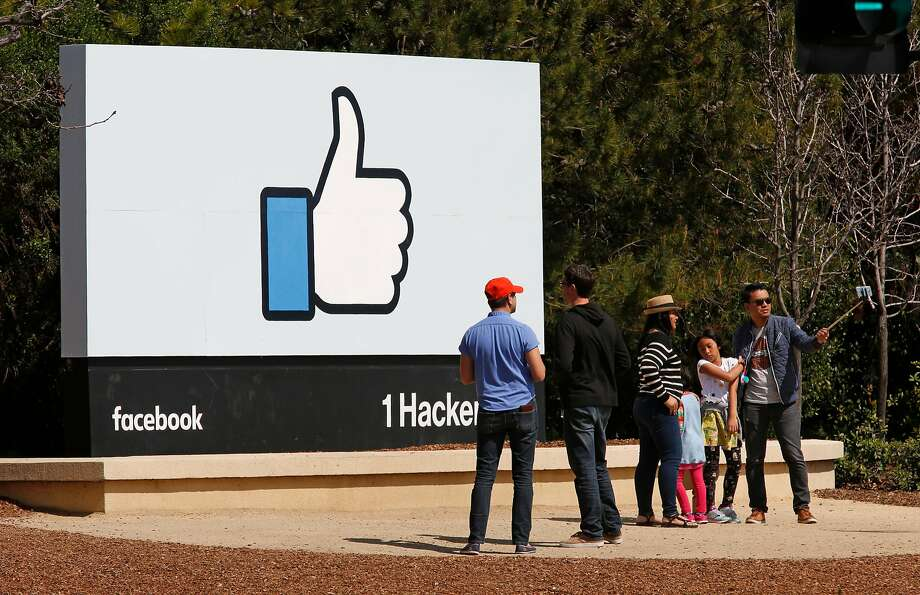 Vistors stop for photos at the Facebook sign in Menlo Park. The social network can track its users across the Internet. Photo: Michael Macor / The Chronicle
