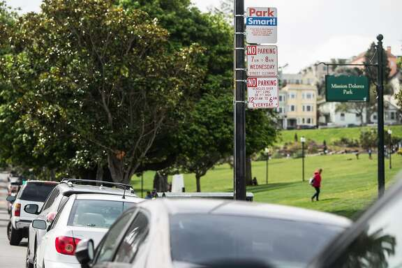"""A sign that reads """"Park Smart"""" sits above a row of cars parked near Dolores Park at 18th and Dolores streets Wednesday, April 11, 2018 in San Francisco, Calif."""