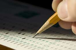 Extreme closeup in dramatic lighting of child's hand marking standardized test form.