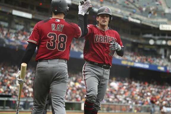 Arizona Diamondbacks' John Ryan Murphy, right, is congratulated by Robbie Ray (38) after hitting a home run off San Francisco Giants' Andrew Suarez in the fifth inning of a baseball game Wednesday, April 11, 2018, in San Francisco. (AP Photo/Ben Margot)