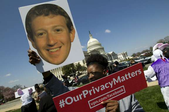 Demonstrator holding up a photo of Facebook CEO Mark Zuckerberg protest outside of the U.S. Capitol in Washington, Tuesday, April 10, 2018, ahead of Zuckerberg's appearance before a Senate Judiciary and Commerce Committees joint hearing. (AP Photo/Jose Luis Magana)