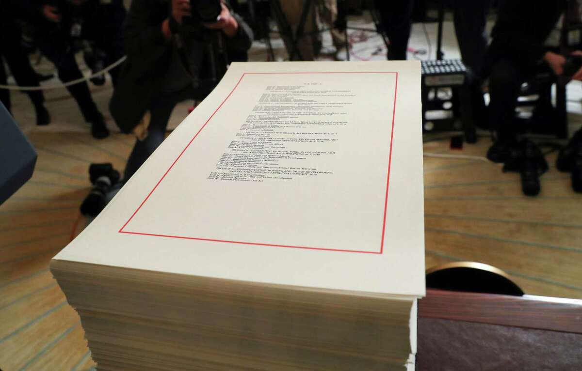 A copy of the $1.3 trillion spending bill is stacked on a table in the Diplomatic Room of the White House in Washington. A new analysis says President Donald Trump's tax cuts and last month's big spending bill will send the federal deficit toward $1 trillion. The Congressional Budget Office says tax and spending bills will push the deficit to $804 billion this year and nearly $1 trillion for 2019.