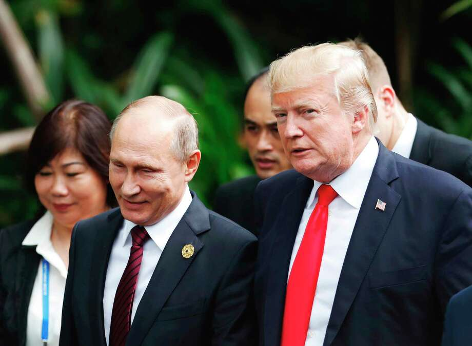 "FILE  - In this Saturday, Nov. 11, 2017 file photo, U.S. President Donald Trump, right, and Russia's President Vladimir Putin, center, talk during the group photo session at the APEC Summit in Danang, Vietnam. The White House has confirmed that U.S. President Donald Trump invited Russia's Vladimir Putin to Washington. Press Secretary Sarah Huckabee Sanders said Monda, APril 2, 2018 that the White House was among ""a number of potential venues"" Putin and Trump discussed during a March 20 telephone conversation. (Jorge Silva/Pool Photo via AP, File) Photo: Jorge Silva / Reuters Pool"