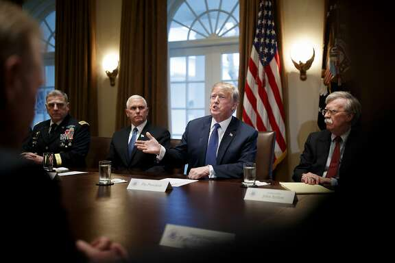 """President Donald Trump is flanked by Vice President Mike Pence, left, and National Security Adviser John Bolton as he meets with senior military leaders at the White House in Washington, April 9, 2018. Trump put Syria and Russia on notice April 11 in a Twitter post, promising that missiles fired at Syria """"will be coming, nice and new and 'smart!'"""" and telling the Kremlin that it should not partner with a """"Gas Killing Animal who kills his people and enjoys it!"""" After the threat, the president said in a separate tweet that relations between the U.S. and Russia are worse than ever. (Tom Brenner/The New York Times)"""