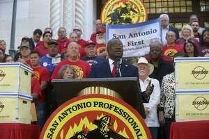 Chris Steele, (center, at lectern) president of the San Antonio firefighters union, speaks Wednesday April 11, 2018 on the steps of City Hall about a petition campaign to call for a city charter amendment election in November. Steele and his supporters delivered thousands of signatures to the city clerk after he and his supporters voiced their opinions outside of city hall.