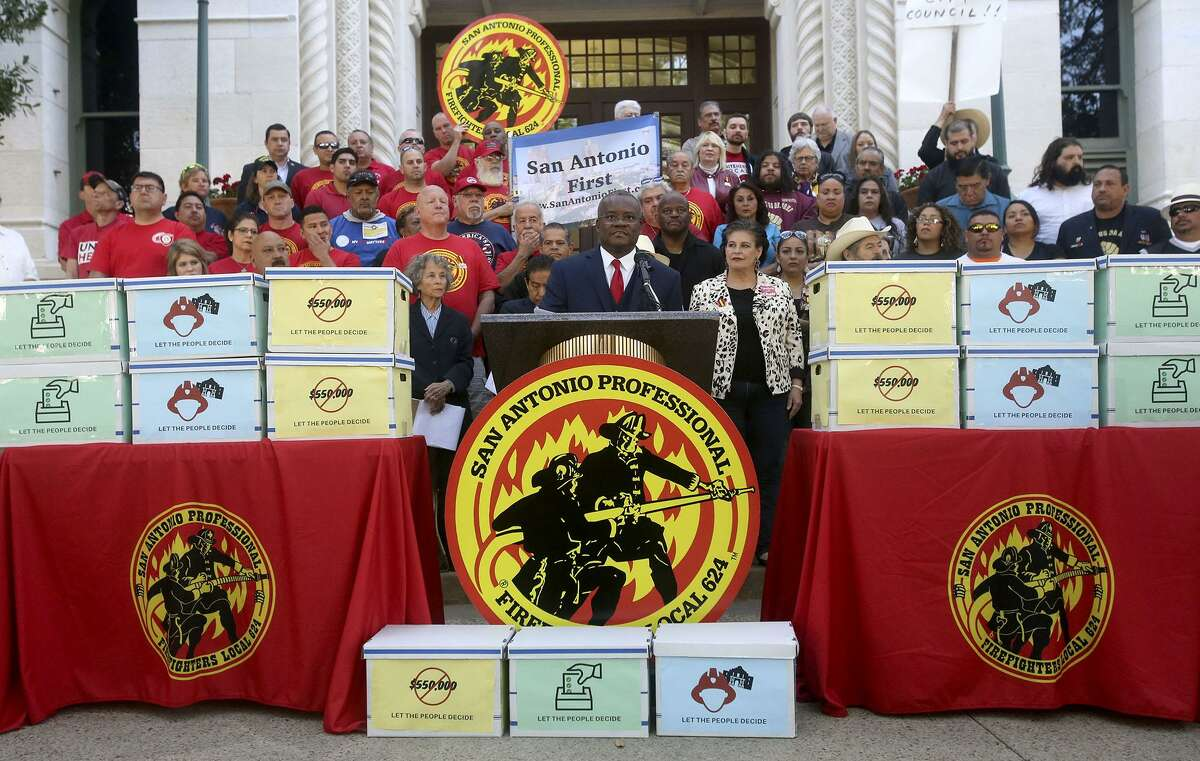Chris Steele, (center, at lectern) president of the San Antonio firefighters union, speaks April 11 on the steps of City Hall about a petition campaign to call for a city charter amendment election in November. These charter amendments are exceedingly bad ideas.