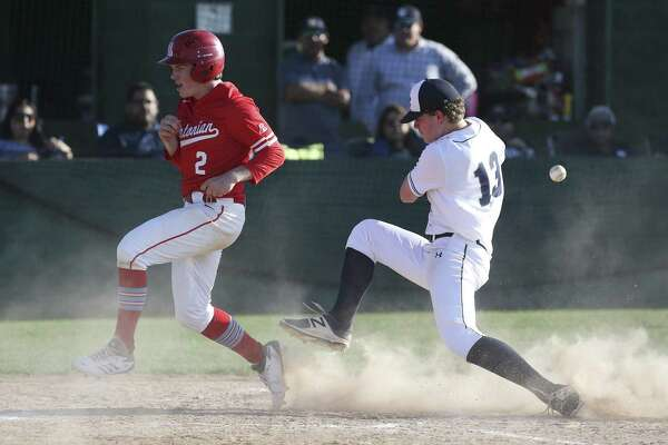 Antonian's Kyle McDonald (02) scores a run in the fifth-inning despite the efforts of Central Catholic pitcher C.J. Marks (13) to tag him out at home plate during their TAPPS 2-I baseball game on Wednesday, Apr. 11, 2018. The Buttons defeated the Apaches, 10-4. (Kin Man Hui/San Antonio Express-News)