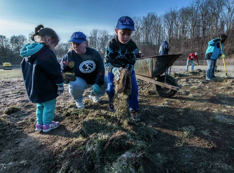 "Diana, 4, mom Danielle, and Alexander Sinkevich, 9, gather  old sod in preparation for new sod at the American Little League field, First Avenue and Krank Street in Albany Wednesday April 11, 2018  in Albany, N.Y. The work continues by volunteers from the ValleyCats, Hannaford and Blue Shield of Northeastern N.Y. all day as part of the ""4 in 24"" program where four little league fields are renovated in less than 24 hours by volunteers.  (Skip Dickstein/Times Union) Photo: SKIP DICKSTEIN / 20043474A"