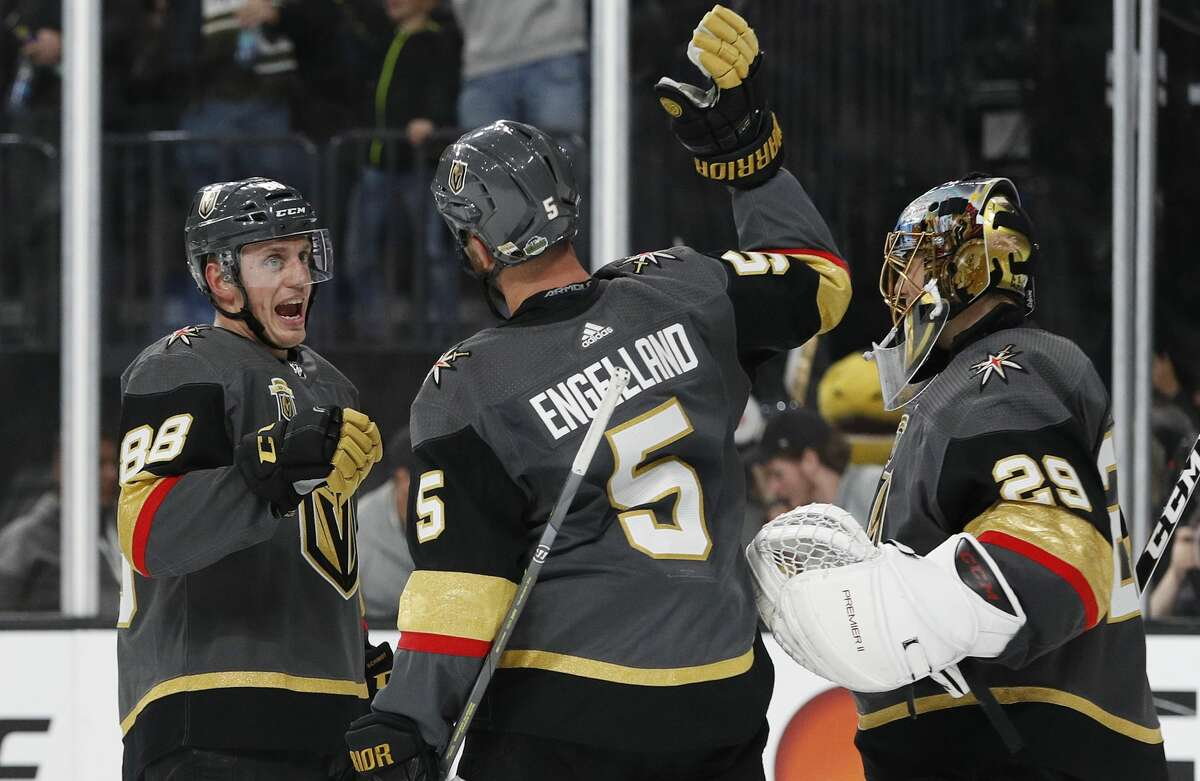 Vegas Golden Knights defenseman Nate Schmidt, defenseman Deryk Engelland and goaltender Marc-Andre Fleury, from left, celebrate the team's 201 win over the Los Angeles Kings in Game 1 of an NHL hockey first-round playoff series Wednesday, April 11, 2018, in Las Vegas. (AP Photo/John Locher)