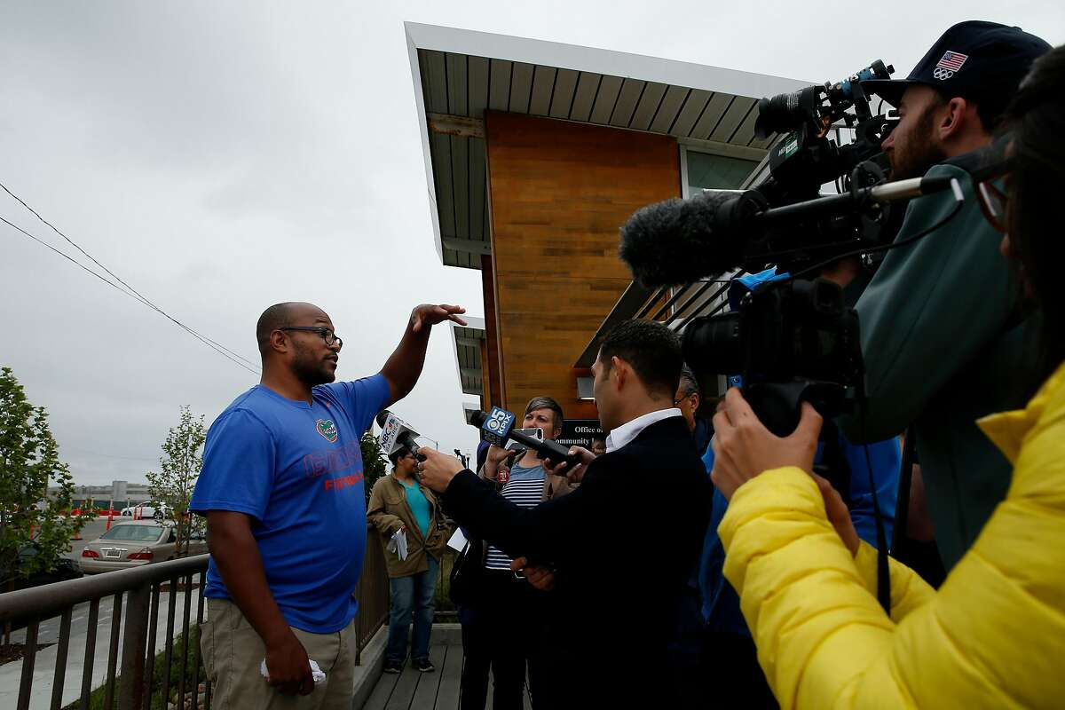 Greenaction's Brian Butler speaks with members of the news media outside the Office of Community Investment and Infrastructure at Galvez Avenue, Wednesday, April 11, 2018, in San Francisco, Calif. Greenaction is an advocacy group for health and environmental justice.