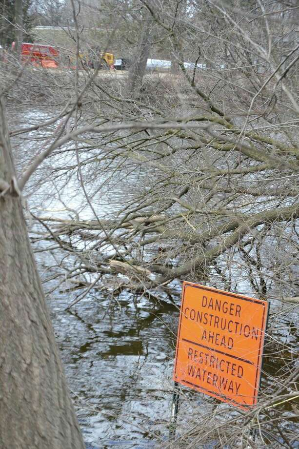 This sign on the Tittabawassee River, just upstream of the Tridge, alerts boaters and anglers to the fact that the riverhas been narrowed in the area of the Robertson Bridge over M-20 while the bridge is being rebuilt (as seen in the background). (Steve Griffin/Hearst Michigan)