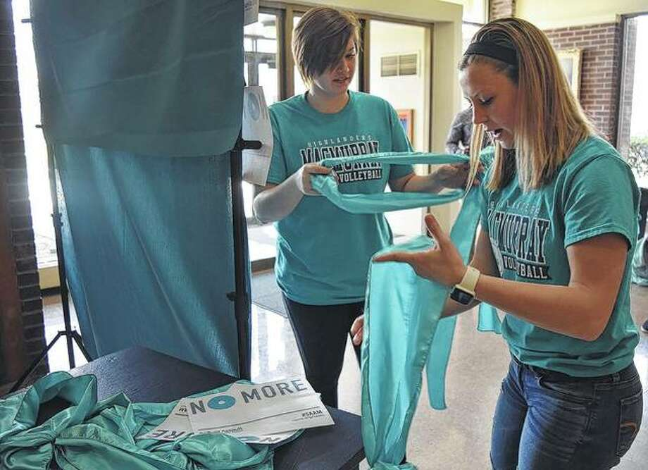 MacMurray College freshman Brenna Rande (left) and sophomore Alexis Moore prepare to take a photo Wednesday during the college's Teal Day. Teal Day is a part of the Sexual Assault Awareness Month activities on campus. Students were encouraged to wear teal and post their pictures to show support against sexual assault. Photo:       Samantha McDaniel-Ogletree | Journal-Courier