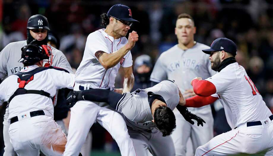 Boston Red Sox relief pitcher Joe Kelly, left, throws a punch at New York Yankees' Tyler Austin, center, as they fight during the seventh inning of a baseball game at Fenway Park in Boston, Wednesday, April 11, 2018. At right is Boston Red Sox first baseman Mitch Moreland. (AP Photo/Charles Krupa) Photo: Charles Krupa / Copyright 2018 The Associated Press. All rights reserved.