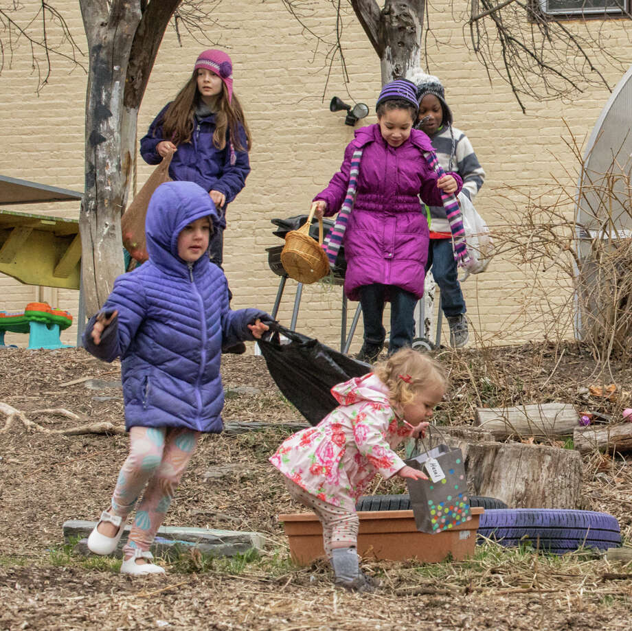 Children and their parents turned out on Easter Sunday for an egg hunt at Gabi?s Community Garden on the corner of Wilbur and Grand streets in Albany?s Mansion Neighborhood. Caleb Tenerowitz, top right, is equipped with a big basket as he waits for the hunt to start. Above, four girls and a boy are on the move looking to fill their baskets and bags with plastic eggs holding chocolate and other treats. Elke van der Laan, at right, smiles with a full basket. Lily Mercogliano and David Easton organized the event with the help of their neighbors. A fine time was had by all despite the cold and rainy weather. Photo: Connie Frisbee Houde / ©2010