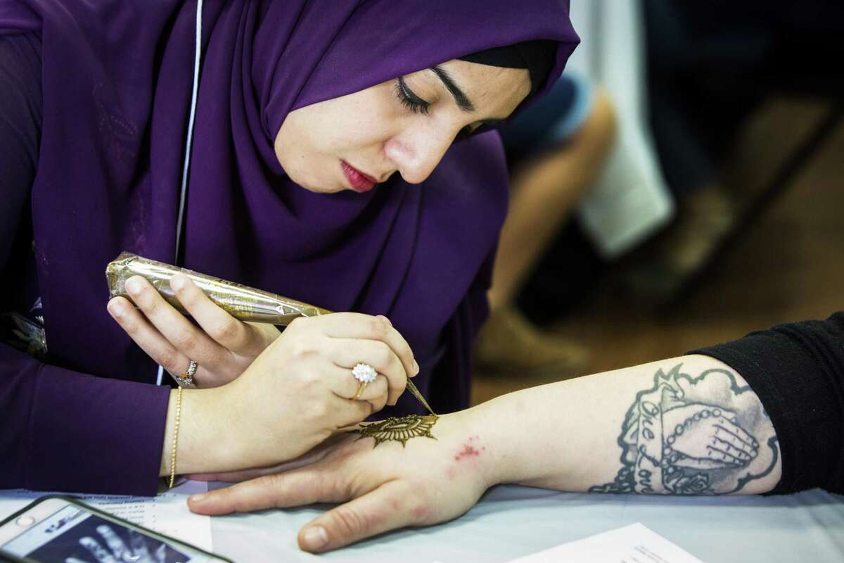 Fatima Yakub, 27, does a henna design on the back of the hand of Stacey Bohm during the Open Mosque Day at the Bear Creek Islamic Center, Saturday, March 10, 2018, in Houston. ( Marie D. De Jesus / Houston Chronicle )