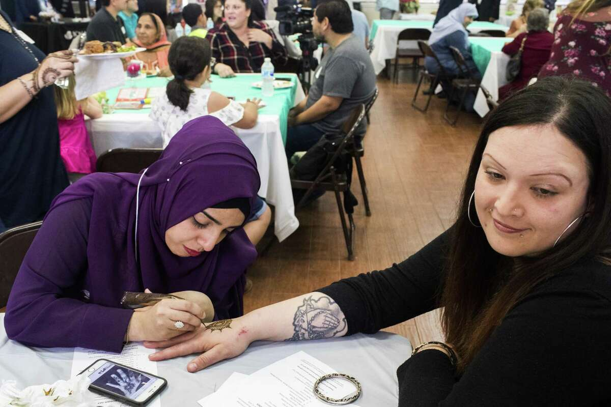 Fatima Yakub, 27, does a henna design on the back of the hand of Stacey Bohm, right, during the Open Mosque Day at the Bear Creek Islamic Center, Saturday, March 10, 2018, in Houston. ( Marie D. De Jesus / Houston Chronicle )