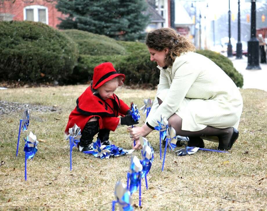 Beatrix Smith, 4, uses all of her force to push a pinwheel into the frozen ground Wednesday, as her mother, Katie Smith, holds the base of the pinwheel for support. The Harbor Beach mother-daughter duo attended the Huron County CA/N Council's Pinwheel Planting event, which is held annually to raise awareness that April is Child Abuse Prevention Month. Photo: Bradley Massman/Huron Daily Tribune